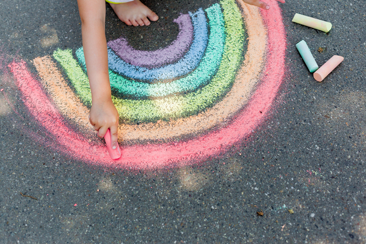 the child girl draws a rainbow with colored chalk on the asphalt. Child drawings paintings concept. Education and arts, be creative when back to school