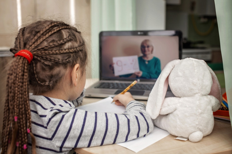 Pretty stylish schoolgirl studying math during her online lesson at home, social distance during quarantine, self-isolation, online education concept
