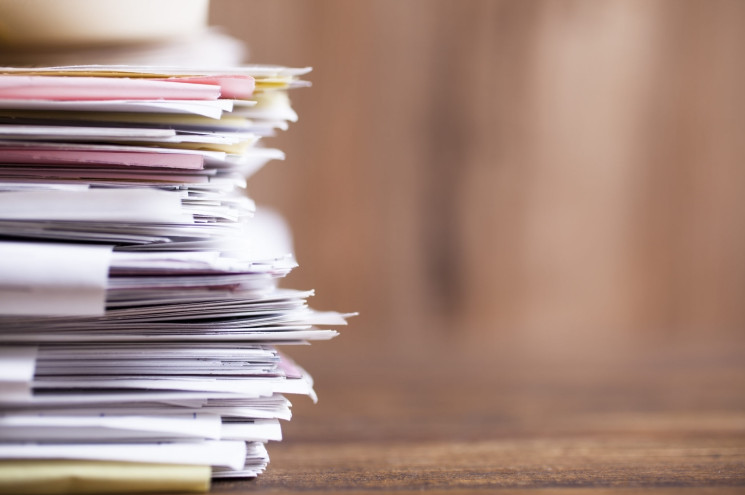 Large stack of multi-colored files and paperwork lie on an office desk.   Wooden background.  Copyspace to side.  No people.